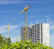 Two tower cranes on construction of multi-story residential buil Royalty Free Stock Photo