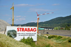 Two tower cranes working on construction site of slovak D1 highway, billboard of Strabag building company in foreground  Royalty Free Stock Image