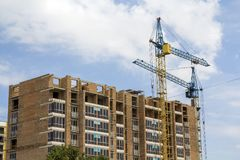 Two tower cranes working on high rise brick building under construction on blue sunny sky copy space background. Modern urbane ar royalty free stock image