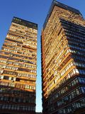 Two towers of an apartment building from below against the sky stock images