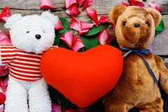 Two Toy bear doll have falling in love with Rose petals background . Two Toy bear doll have falling in love with Rose petals background in valentine day royalty free stock photo