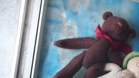 Two toy bears laying on a windowsill