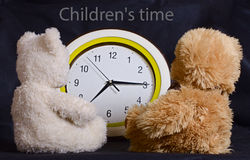 Two toy bears look at the watch Stock Image