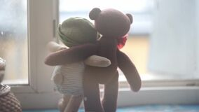 Two toy bears standing in hugs on a windowsill