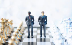 Businessmen on chessboard. Two toy businessmen, lawyers or politicians on a chessboard. Business, politics or law concept Royalty Free Stock Images