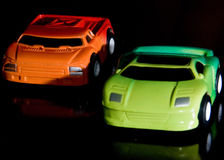 Two Toy Cars. Sit on a black table with dynamic constrasted lighting Royalty Free Stock Photo
