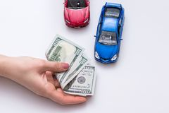 Two toy cars with cash in hand.  Stock Images
