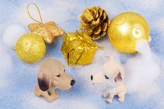 Two toy dogs sit next to Christmas decorations. stock photography