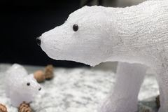 Two toy glass polar bears on a dark background. Two toy glass polar bears on a dark background with snow and fir cones Stock Photos