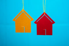 Two toy houses with blue blurred background. Toy houses hanging from a rope on the background wall with blurred background Stock Photos