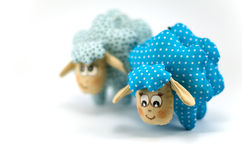 Two toy lambs, one focused blue speckled  second turquoise speckled not in focus on white background Royalty Free Stock Photography