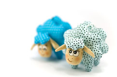 Two toy lambs, one focused turquoise speckled second blue speckled not in focus on white background Royalty Free Stock Image