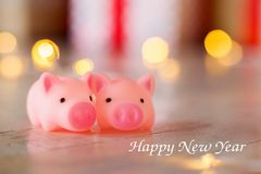 Two toy a pig against the background of New Year`s scenery, bokeh. Inscription Happy New Year stock photo