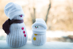 Two toy snowmen on blurry background. Two toy snowmen outside, on blurry background Royalty Free Stock Photo