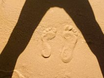 Two tracks of human feet in the sand art. In the corner shadows on yellow sand printed two tracks of bare feet, one larger the other smaller shadows accentuate Stock Photos