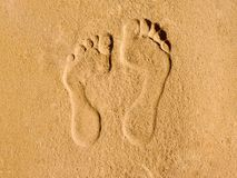 Two tracks of human feet in the sand art. On yellow sand printed two tracks of bare feet, one larger the other smaller shadows accentuate the contour line image Royalty Free Stock Photo
