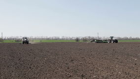 Two tractor with plow and drill. Tractor with plow seeder and unfold on the field near the black soil of winter stock video