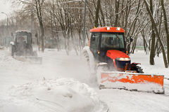 Two tractor snow removal in the park Stock Images
