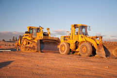 Two Tractors. Yellow tractors under sunset in cosntruction site Stock Photography