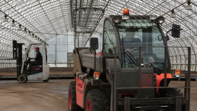 Two tractors lifts in the greenhouse. Agriculture - two tractors working in the nursery greenhouse stock footage