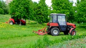 Two tractors are mowing the grass in the park in Moscow district Ramenki. stock video footage
