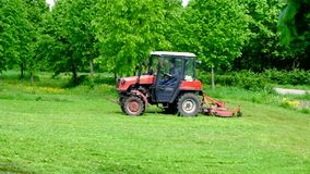 Two tractors are mowing the grass in the park in Moscow district Ramenki. stock video