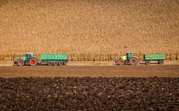 Two tractors are ready to take away harvest of corn at autumn fields Royalty Free Stock Images