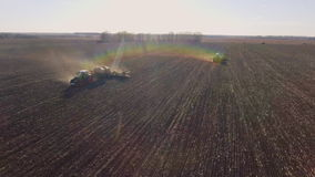 Two tractors sow the field in the spring. Shooting before sunset, beautiful highlights and rainbow effect. 4K video stock video footage