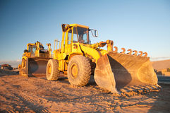 Two Tractors at Work. Two yellow tractors in construction site under blue sky Stock Images