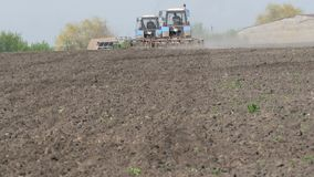 Two tractors work in field in early spring stock footage