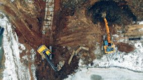 Two tractors work at a quarry, digging earth. Heavy machinery at a construction site.