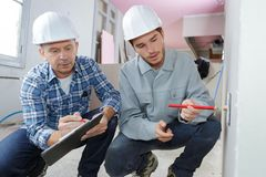 Two tradesman crouched with clipboard royalty free stock photos