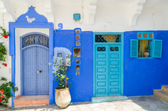 Two traditional blue wooden doors on white and blue Moroccan building, Asilah, Morocco, North Africa Stock Photo