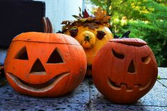 Two traditional carved halloween jack o lanterns in front and one non carved in back, placed on forefront on stone tiled floor. Evening sunshine royalty free stock photos