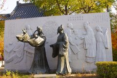 Two Traditional dressed Chinese statue and a stone engraving architectures in a park