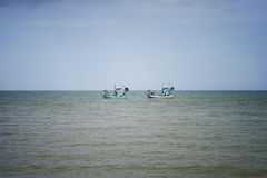 Two traditional fishing boat sailing on the sea, blue sky background Stock Photo