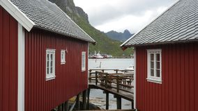 Rorbuer. Two traditional fishing wooden cabins on the stocks called rorbuer and view throough them to the rocks and mountains, Lofoten peninsula, Norway Royalty Free Stock Images