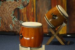 Two traditional Japanese taiko drums on a stage with painted decor in the background royalty free stock image
