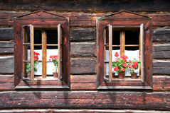 Two Traditional Opened Woden Windows with Flowers. Two Traditional Opened Wooden Windows with Red Flowers Royalty Free Stock Image