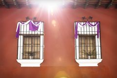 Two traditional windows with semana santa ribbon decoration and sunbeam in Antigua, Guatemala. Two traditional windows with purple white semana santa easter royalty free stock images