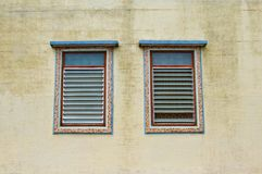 Two traditional windows on the yellow wall Stock Photos