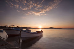 Two traditional wooden fishing boats in the sea. Fishing boats tied up in harbor at the end of the day Stock Photo