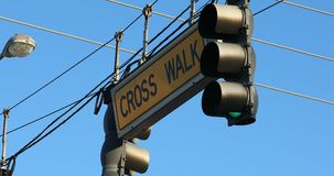 Two Traffic Lights Hanging On A Cable. Two Traffic Lights With Cross Walk Sign Hanging On A Cable Over The Road Against The Blue Sky On International Drive In stock video footage