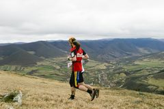 Two trail runners and a mountain village Stock Photos