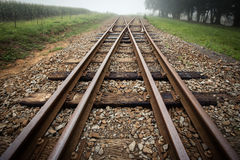 Two Train Tracks meet. Train tracks cross over and go off into the distance stock photography