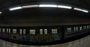 Two trains leaving underground station. Wide angle shot of two underground trains leaving station in opposite directions. Trains decorated with graffiti stock video footage