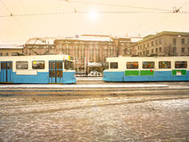Two tram by in opposite directions with water season Royalty Free Stock Photography