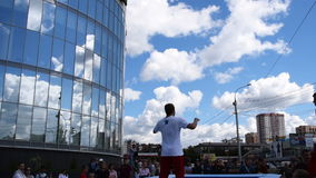 Two trampoliners doing tricks. NOVOSIBIRSK, RUSSIA AUGUST 14, 2015: Public sport event. Viwers watching young two young sportsmen jumping on tramp and doing stock video footage