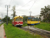 Two trams in Khabarovsk. Red and yellow trams on Amur boulevard Royalty Free Stock Images