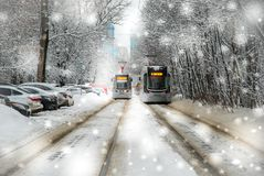 Two trams in a snowfall. On a frosty day in winter Royalty Free Stock Photos